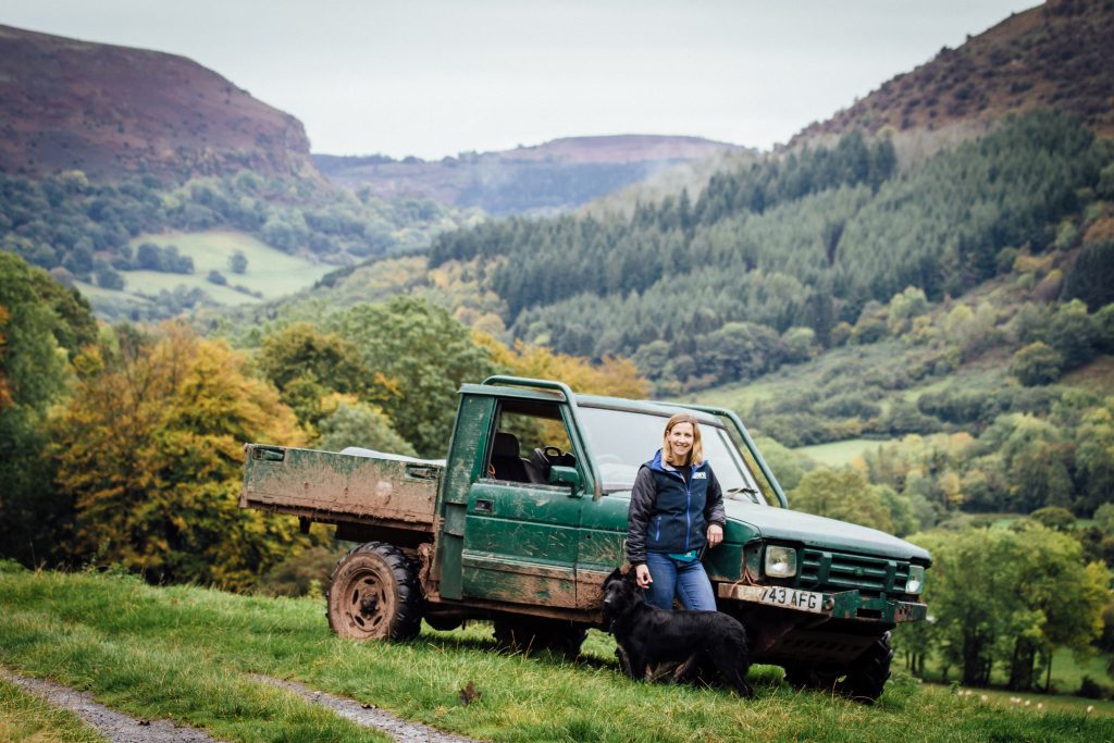 shepherdess with her 4x4 with the llanthony valley behind.