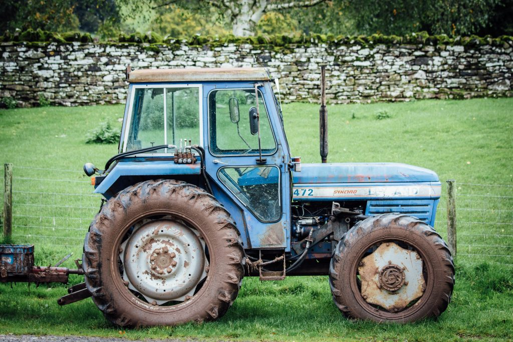 old blue tractor on the farm yard